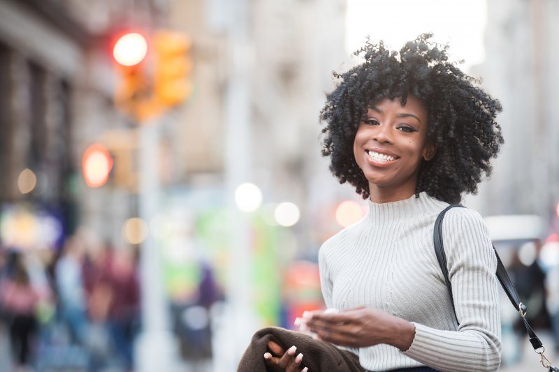 a young woman walking on a street and smiling, showing off her healthy, fully intact smile